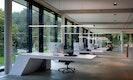 Die futuristischen Tische und  die Manufakturleuchte Glide von Ueberholz bestimmen das Büroerlebnis
